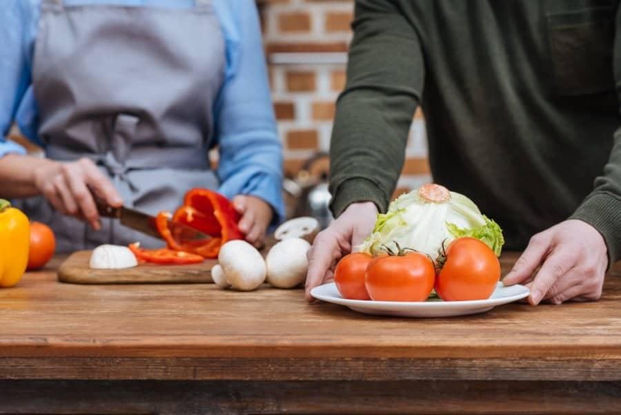 Værtspar forbereder maden til de får gæster på besøg